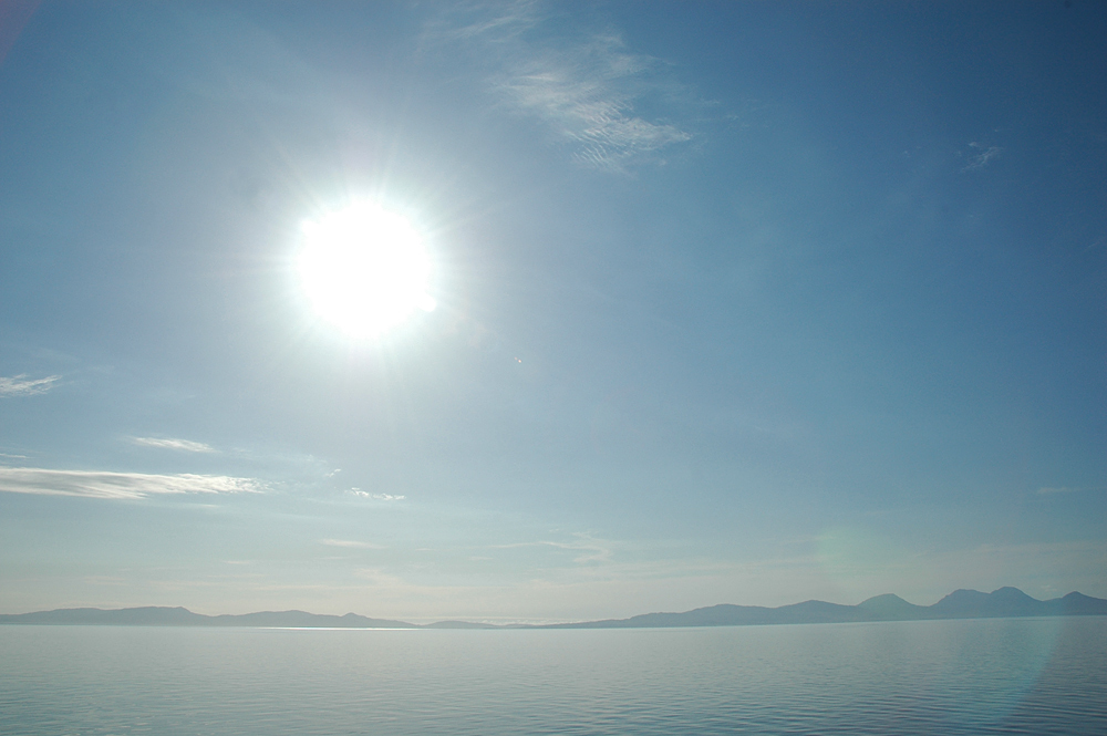 Picture of a bright sun on a clear sky over the sea, two islands in the distance
