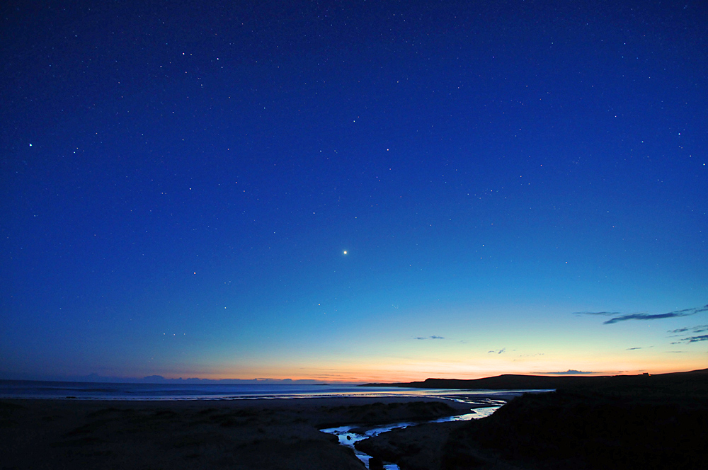 Picture of the sky with stars above a beach during the gloaming