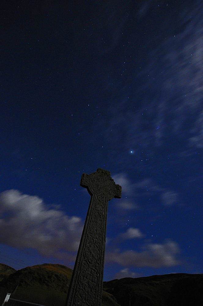 Picture of a Celtic cross at night under a starry sky