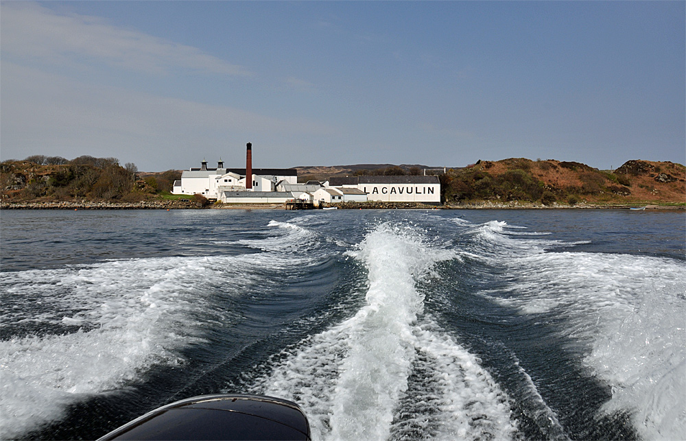 Picture of Lagavulin distillery seen from a speedboat, the wash in view