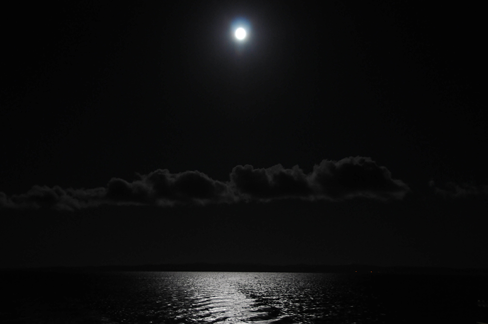 Picture of the moon illuminating the sea on a ferry crossing, clouds in the distance
