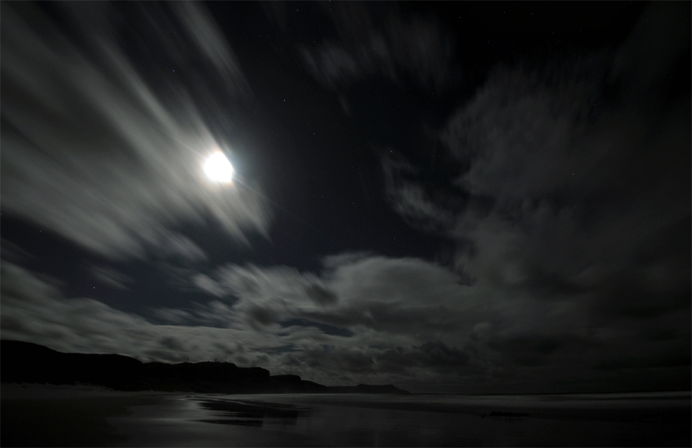 Picture of a moonlit bay with a wide beach, some clouds in the sky
