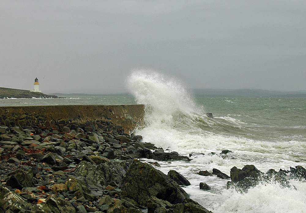 Picture of a wave breaking over a small pier, a lighthouse in the distance behind