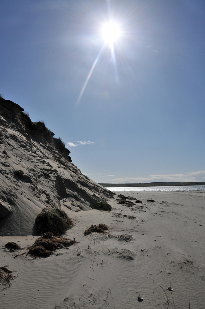 Picture of bright sun over dunes and a beach next to a sea loch