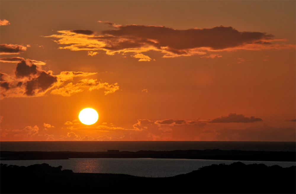Picture of a sunset over a loch, the sea in the background