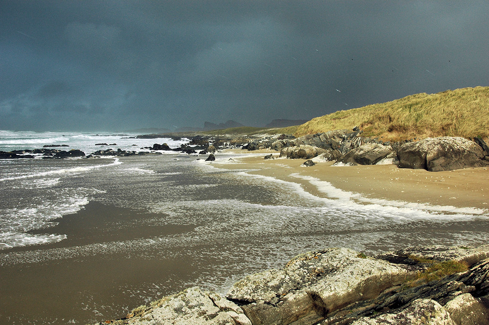 Picture of a beach with dark storm clouds above, waves and foam washing on to the beach