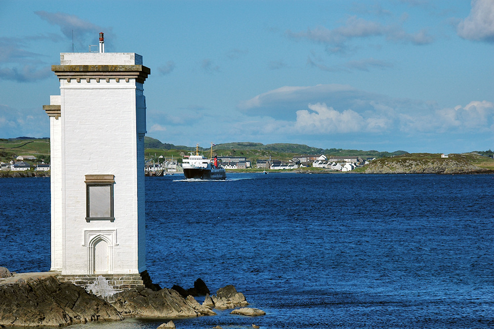 Picture of a ferry leaving a small port past a white square lighthouse