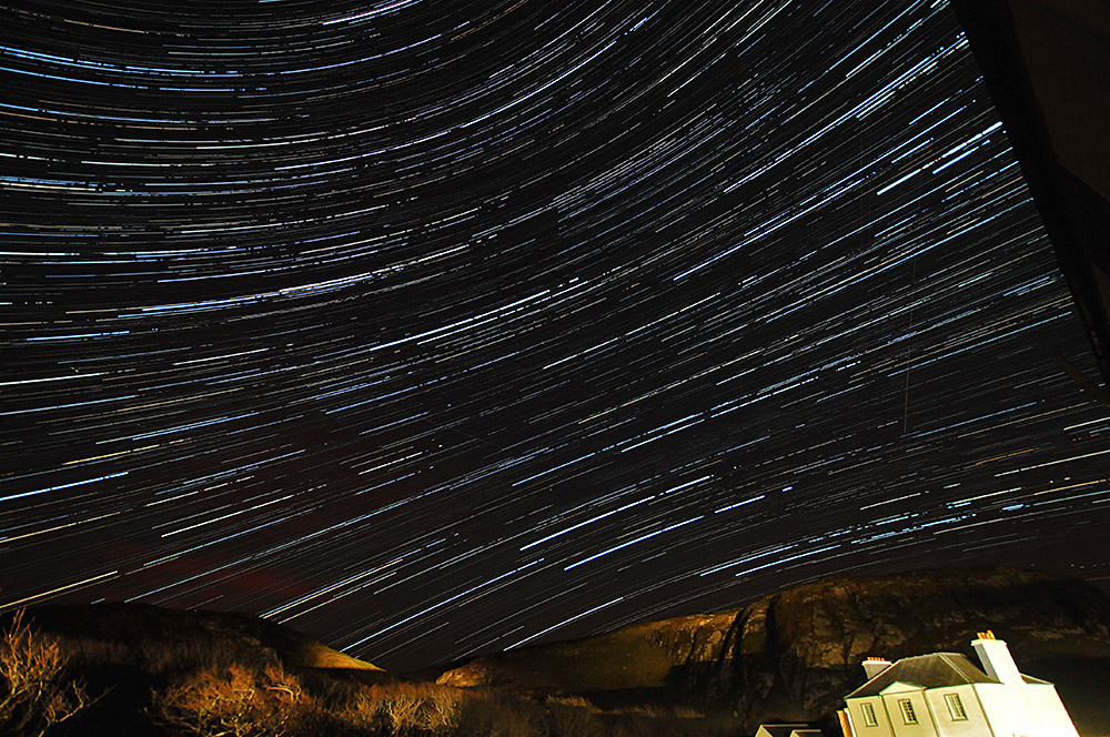Picture of startrails above crags and a large house