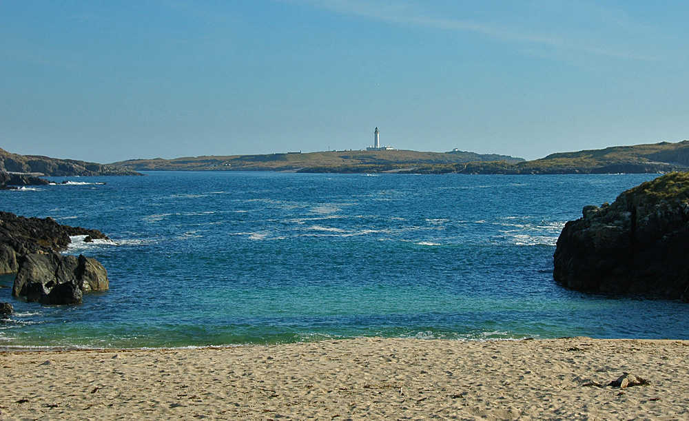 Picture of a lighthouse on an offshore island, seen from a beach