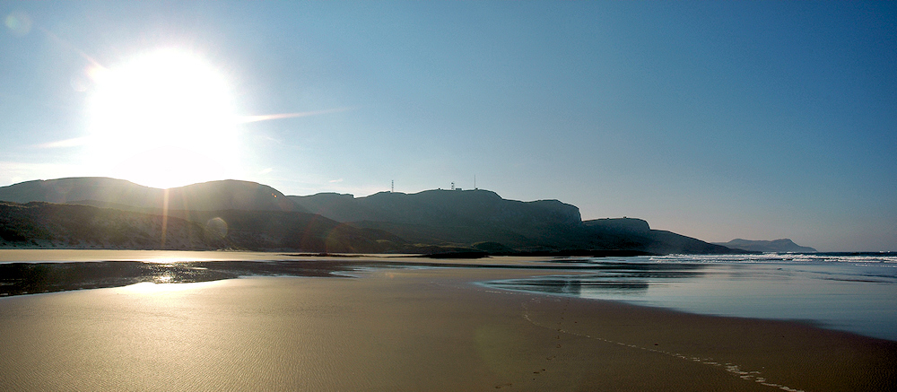Picture of a sunrise above the crags next to a wide sandy bay