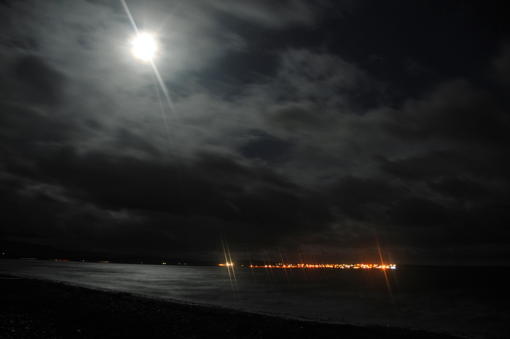 Picture of a view over a moonlit loch with the lights of a village on the other side