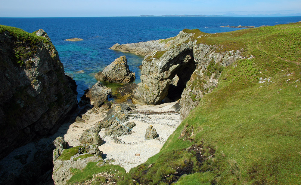 Picture of a natural arch in cliffs on a northern coast