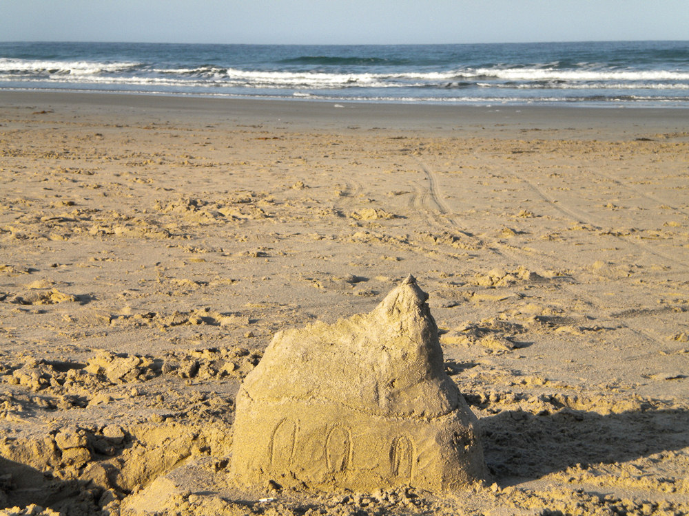 Picture of a small church built from sand on a beach