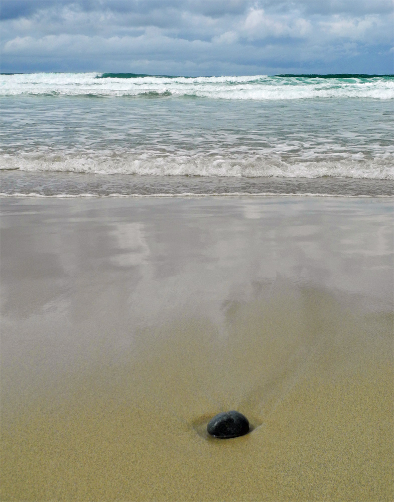 Picture of a stone on a beach, the surf washing over it