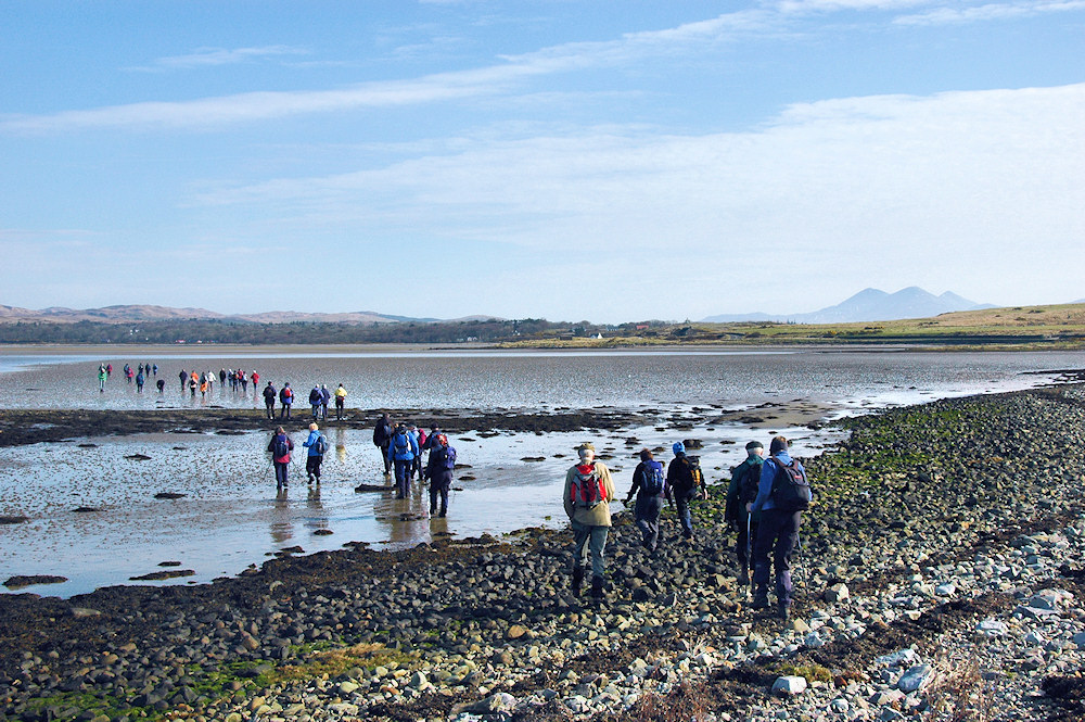 Picture of walkers crossing the top of a sea loch at low tide