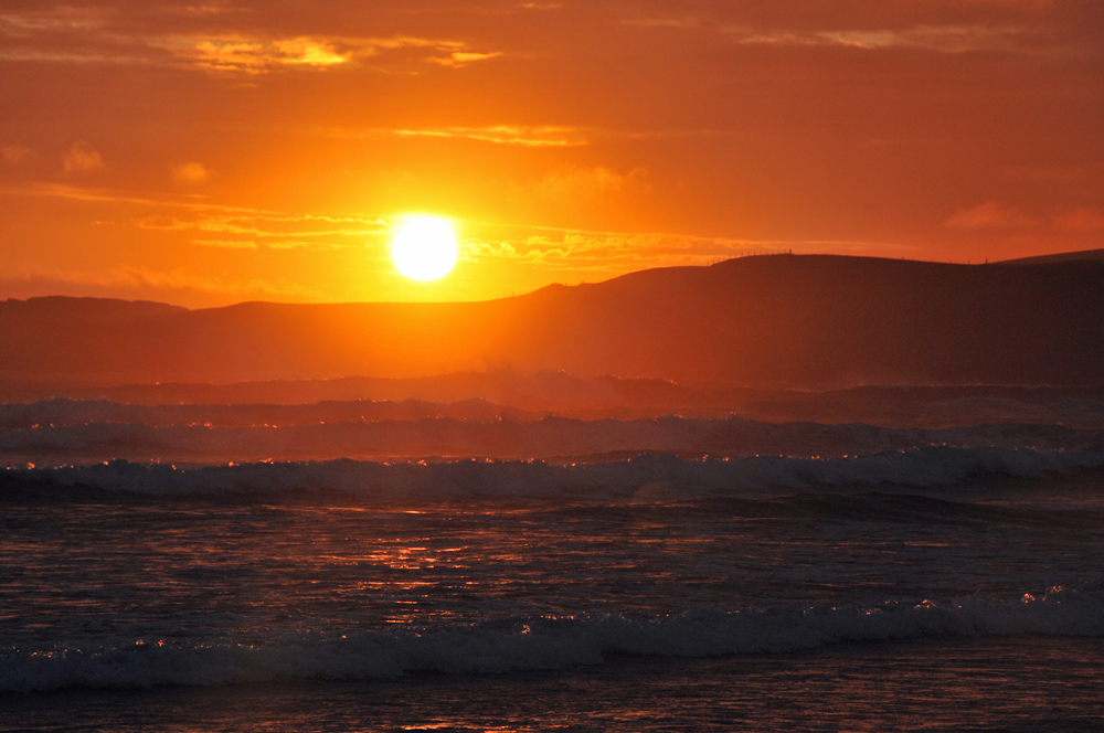 Picture of waves at sunset, low hills in the background