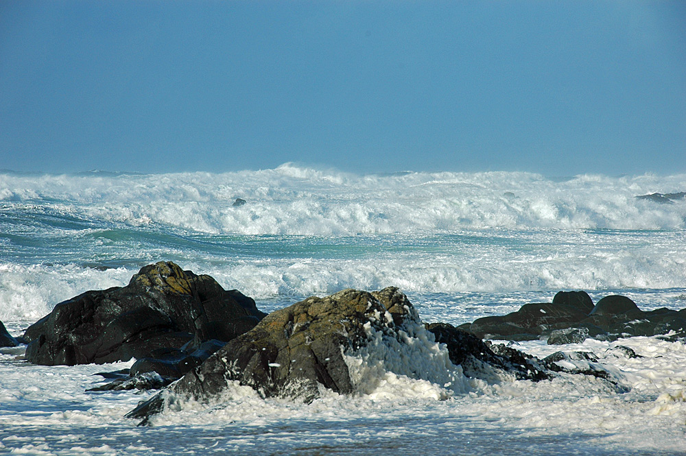 Picture of waves breaking towards rocks on a beach, foam on the beach
