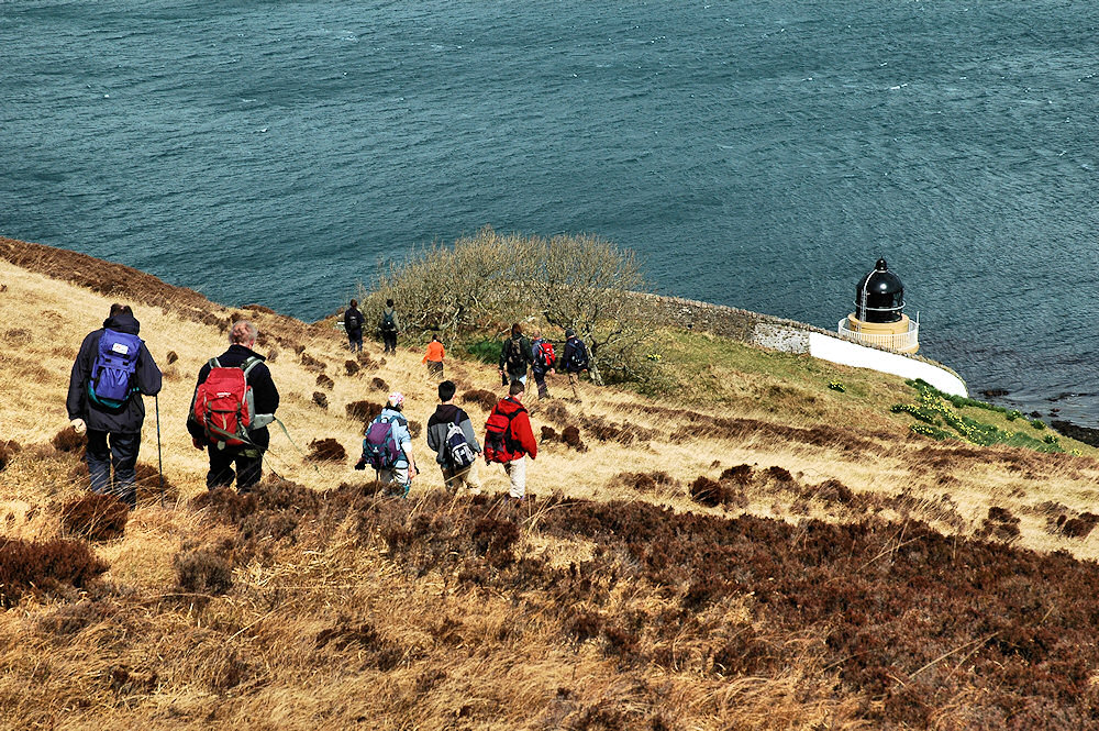 Picture of a group of walkers approaching a lighthouse, descending a hill