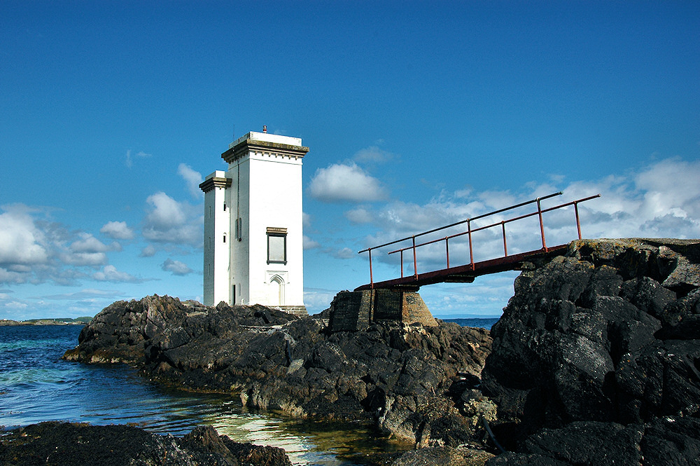 Picture of a square lighthouse with a footbridge leading to it