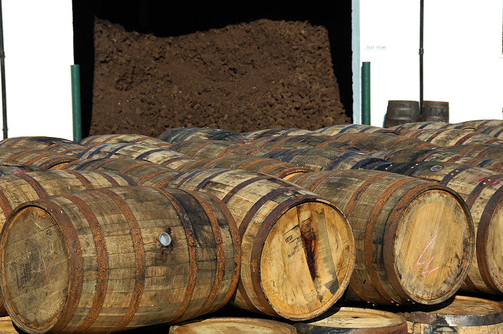 Picture of whisky casks in front of a peat store at a distillery