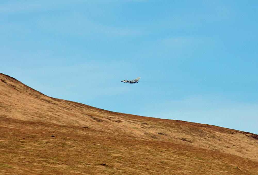 Picture of a fighter jet flying low over a hilly landscape