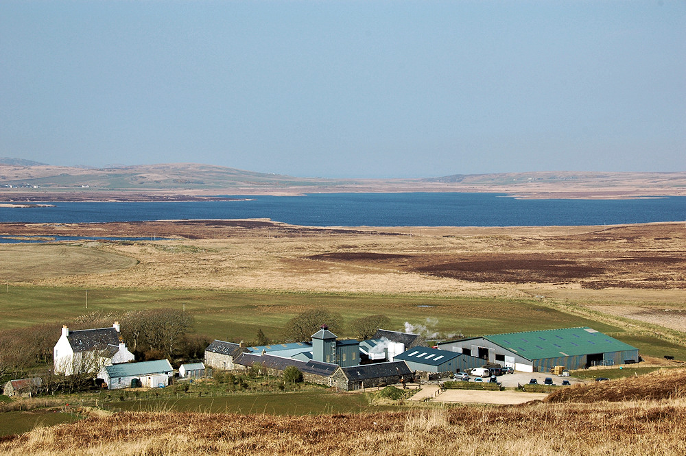 Picture of a distillery on a farm, a loch in the background