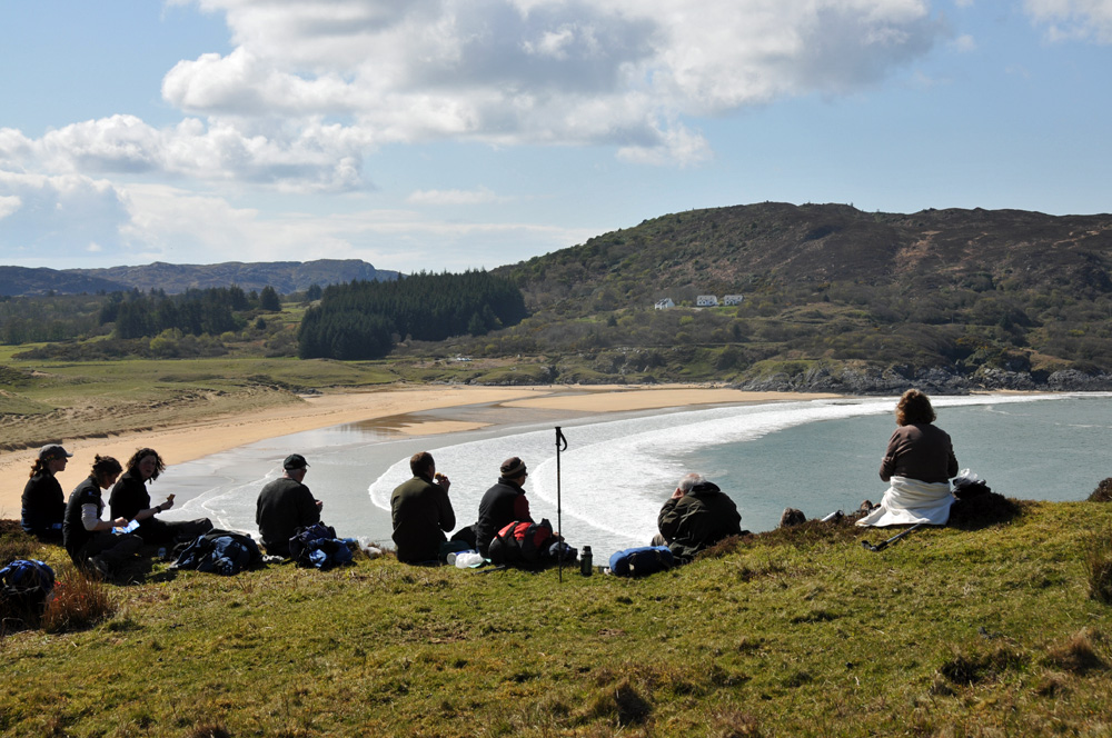 Picture of walkers enjoying a lunch break on cliffs high above a bay with a beach