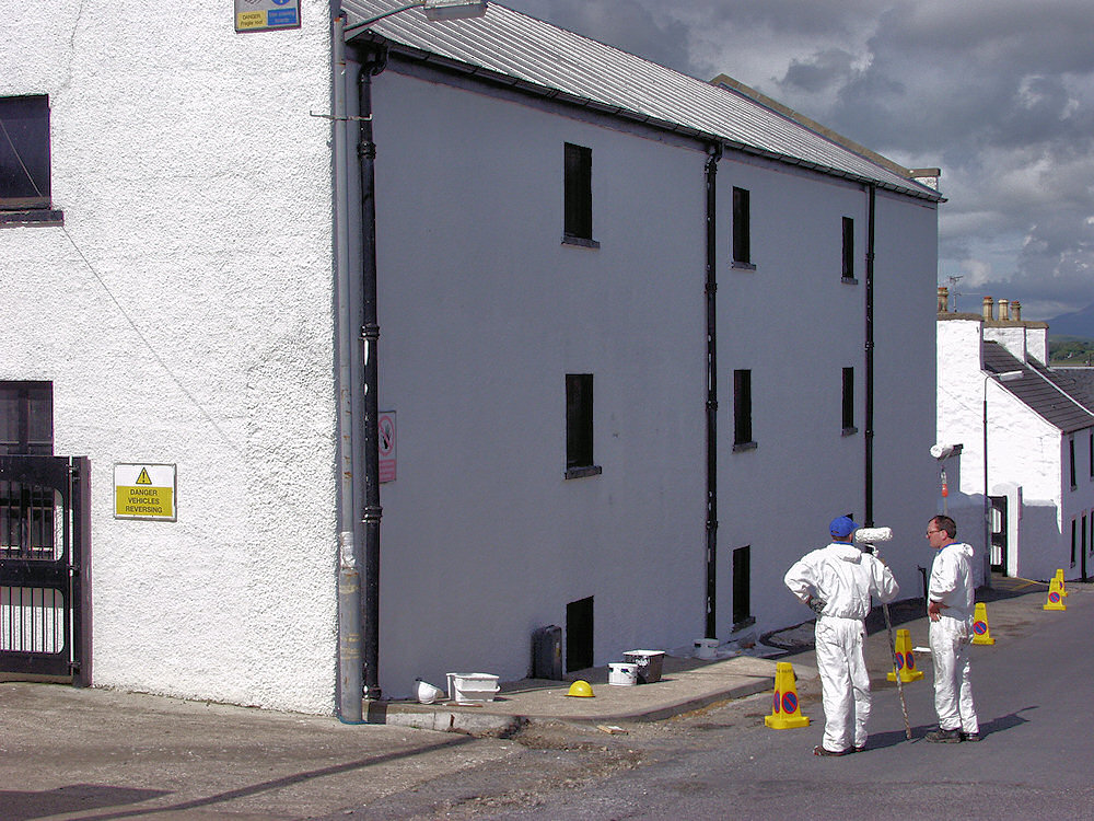 Picture of two men in white painter overall standing next to a whitewashed building
