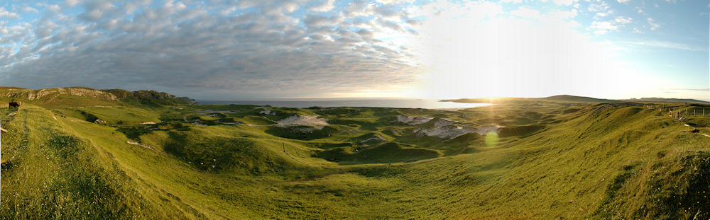 Panoramic picture of a view over dunes and a bay at sunset