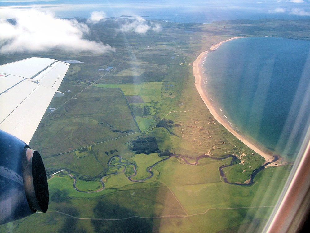 Picture of a bay with a beach and a river running towards it, seen from a plane