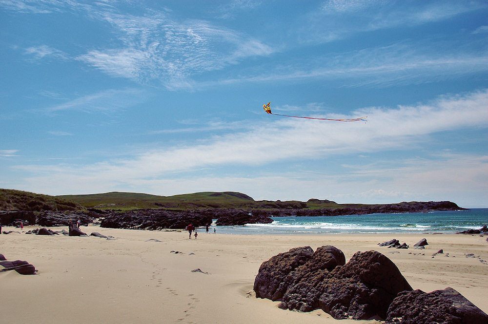 Picture of a beach on a sunny day with a family flying a kite