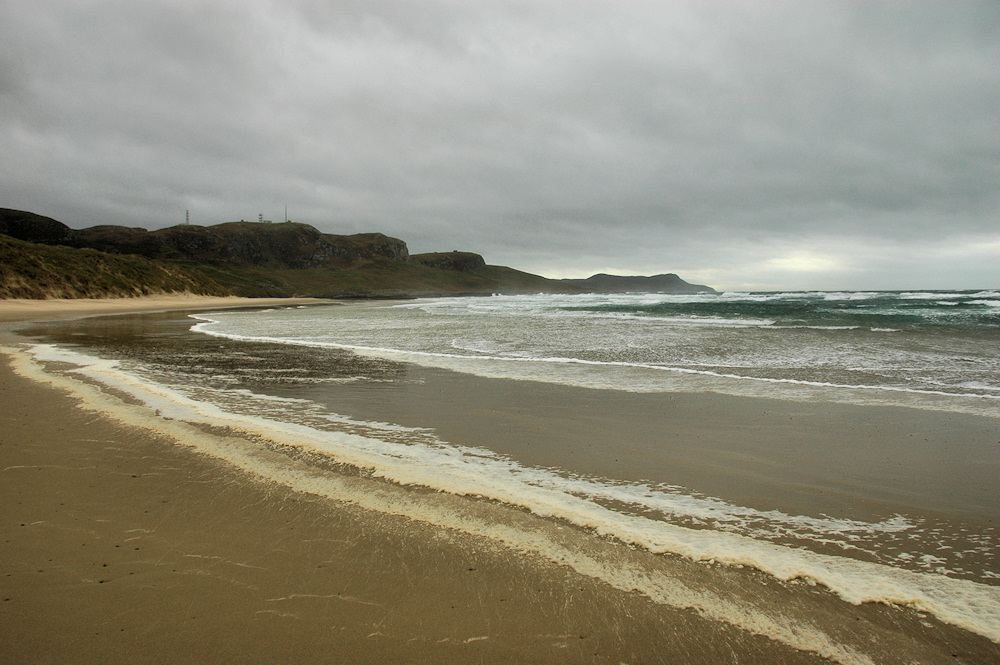 Picture of a beach with foam under grey clouds