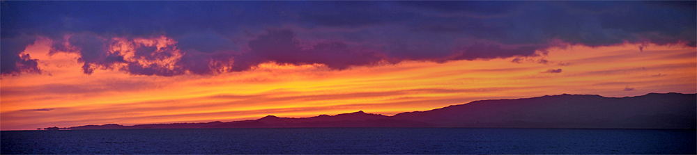 Panoramic picture of a colourful sunset over an island, seen from a ferry