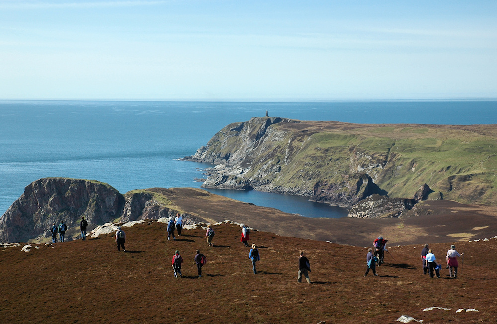 Picture of walkers on high cliffs with a monument in the distance