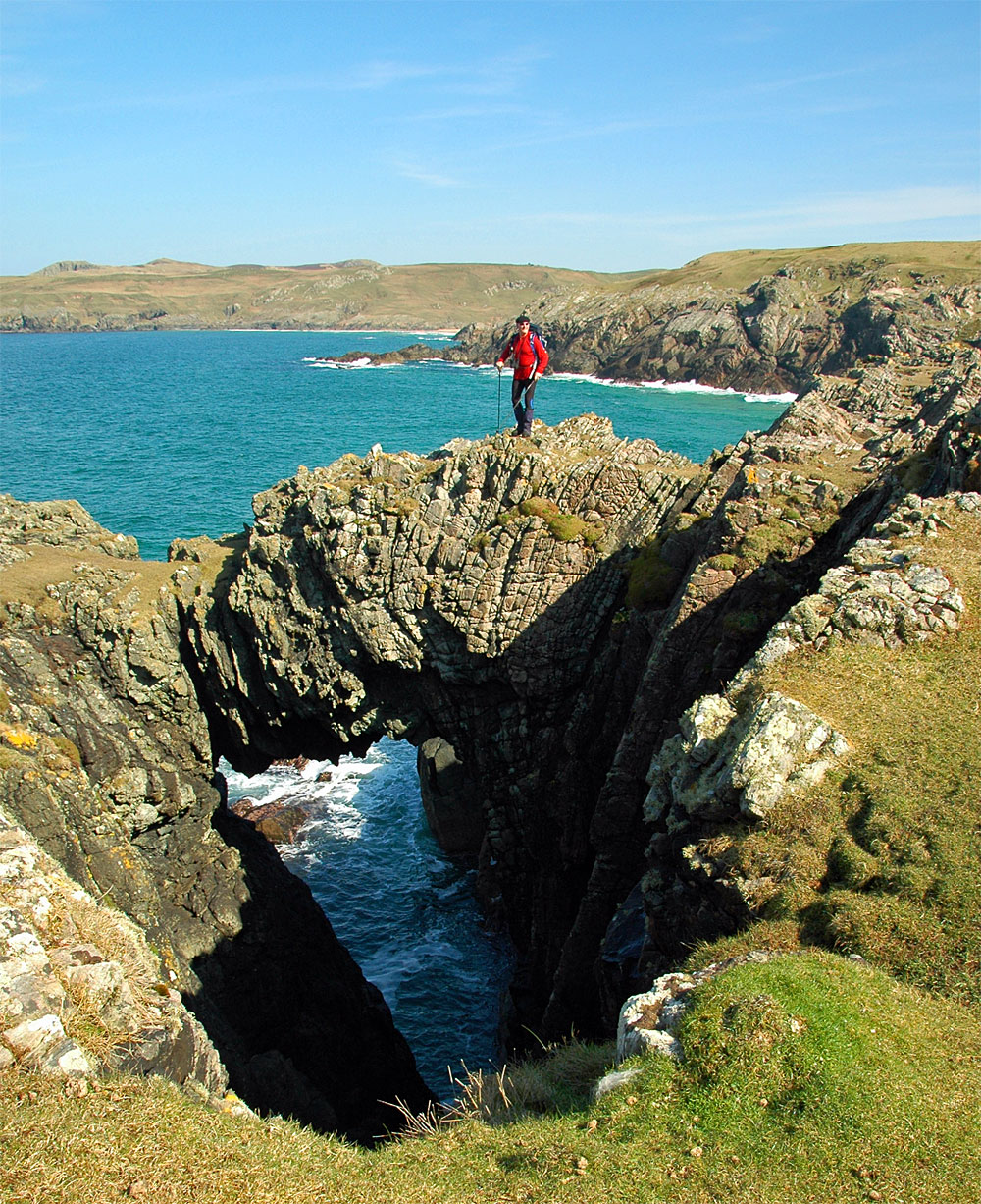 Picture of a walker on top of a natural arch in cliffs along a shore