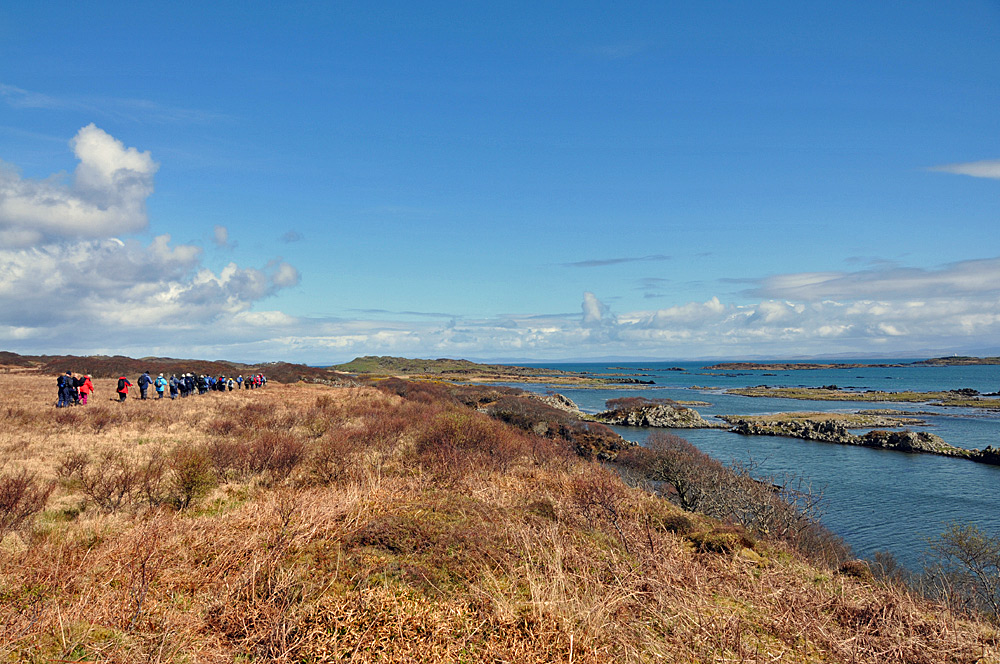 Picture of walkers along a coast with skerries offshore