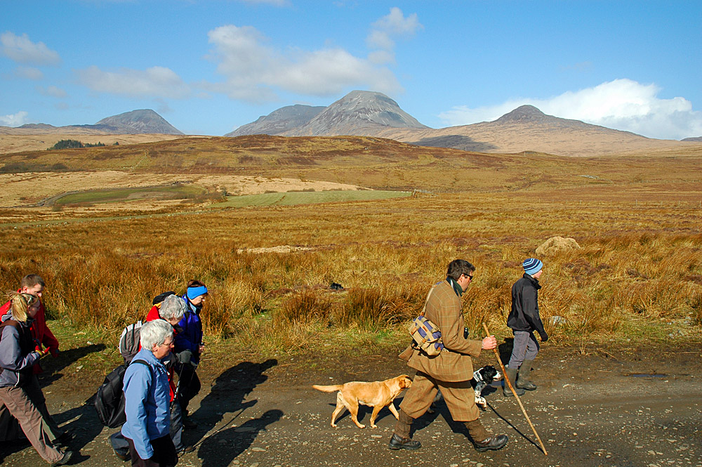 Picture of walkers on a track with the Paps of Jura in the background