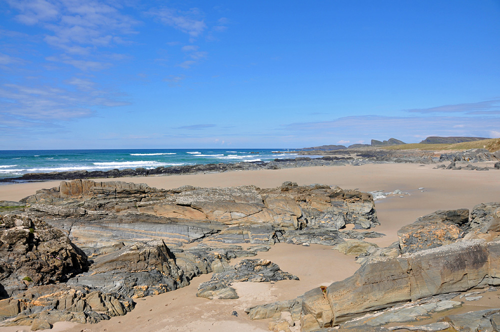 Picture of a wide bay with a sandy beach with rock formations