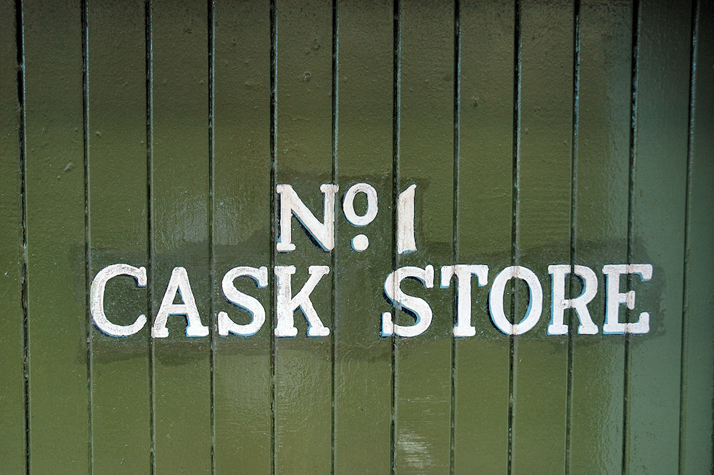 Picture of a green door with the writing Ardbeg No.1 Cask Store