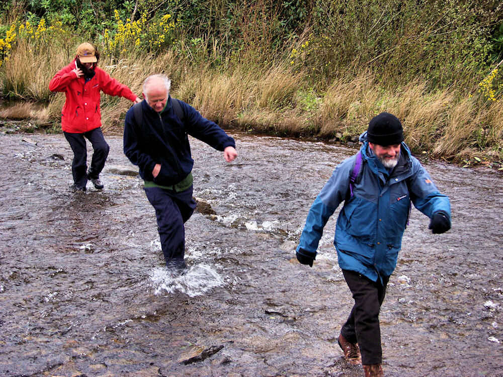 Picture of three walkers crossing a burn