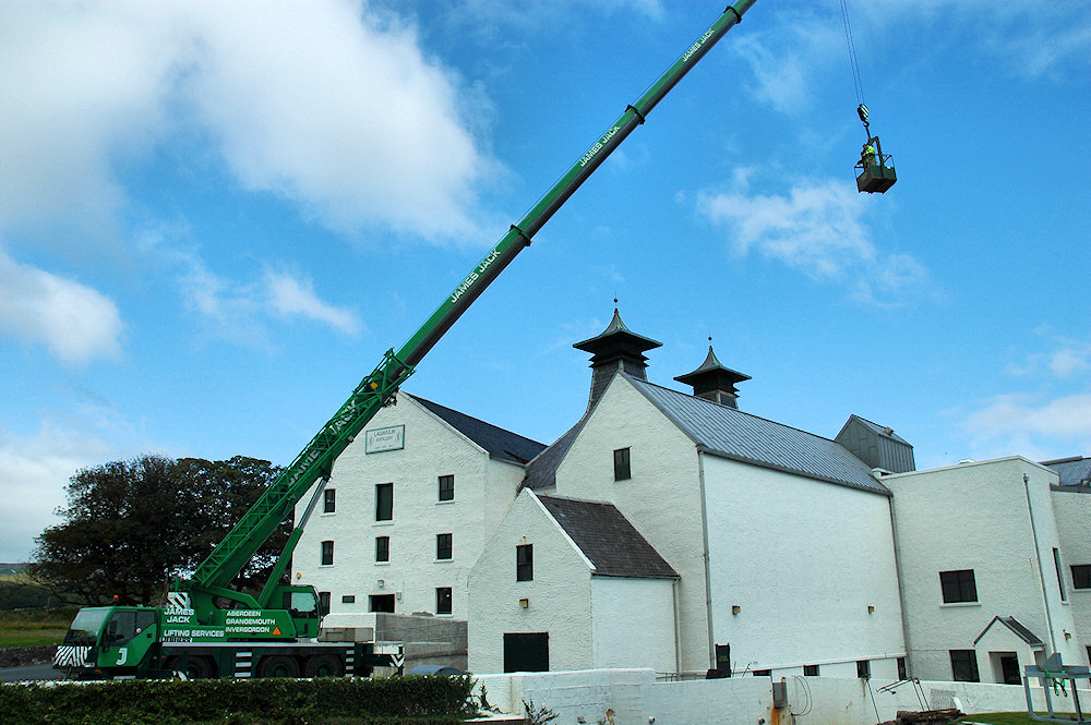 Picture of a large mobile crane at a white washed distillery building