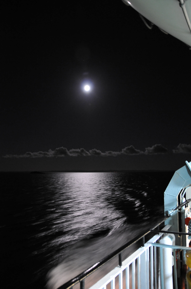 Picture of the Moon seen over the sea from a ferry, reflections in the water