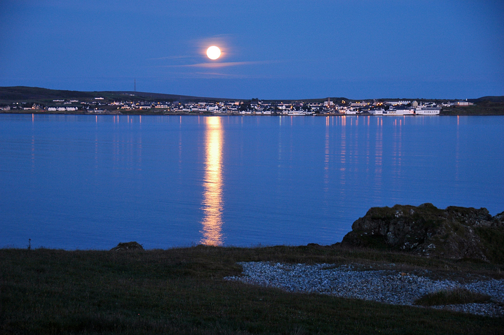 Picture of a full Moon over a coastal village on a clear calm evening, seen across a sea loch