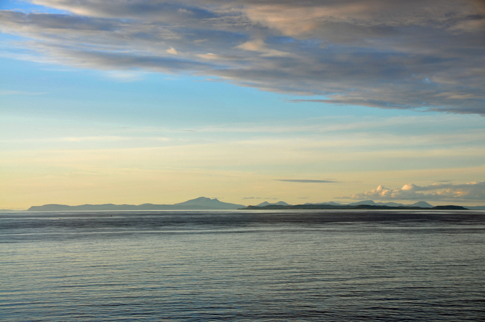 Picture of a view of two islands from a third island on a summer evening