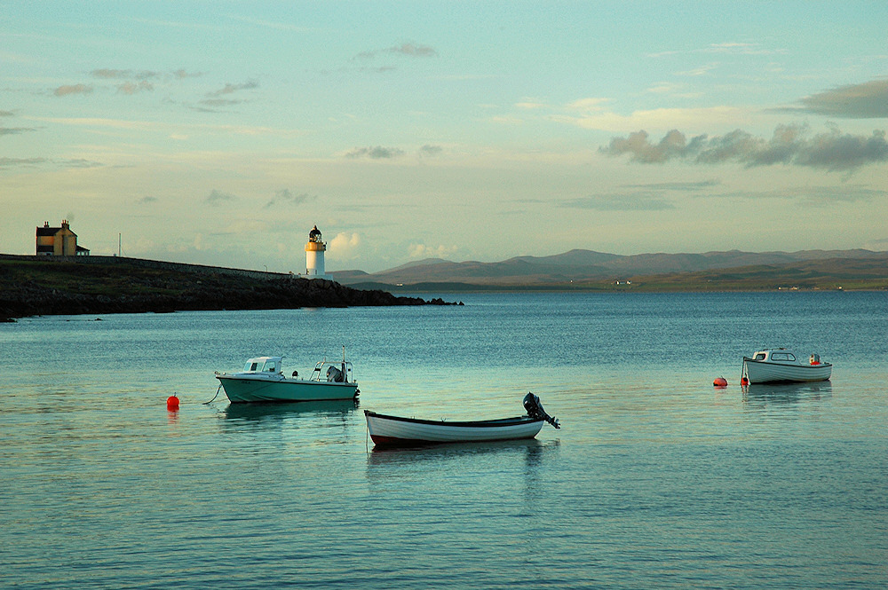 Picture of a view over a calm sea loch with anchored boats and a lighthouse