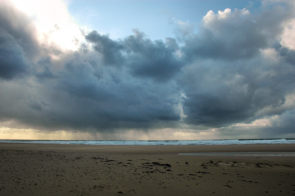 Picture of big rain shower clouds approaching a beach