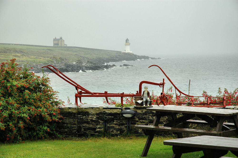 Picture of a view over to a lighthouse in the rain