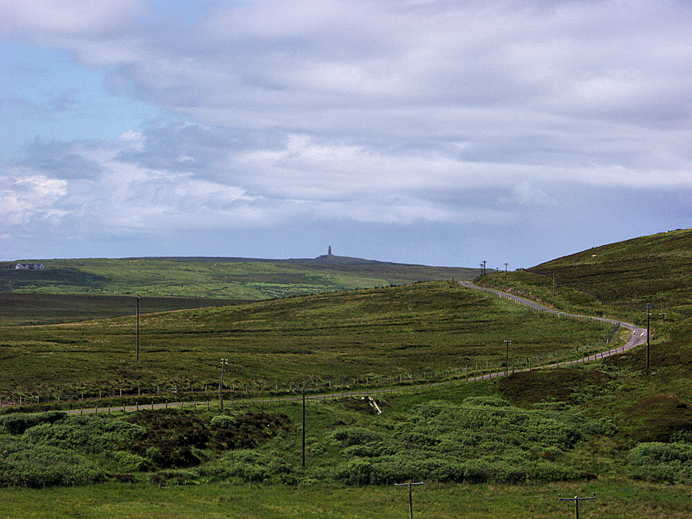 Picture of a wide landscape with a single track road, a monument in the distance