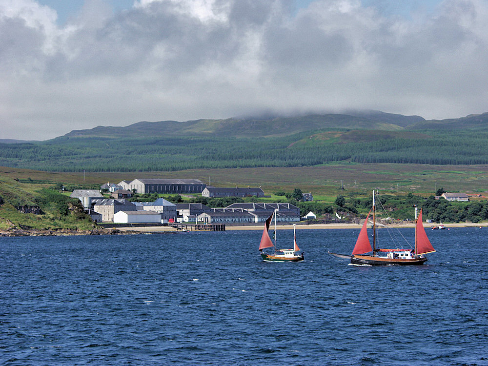 Picture of two sailing boats passing a small village with a distillery
