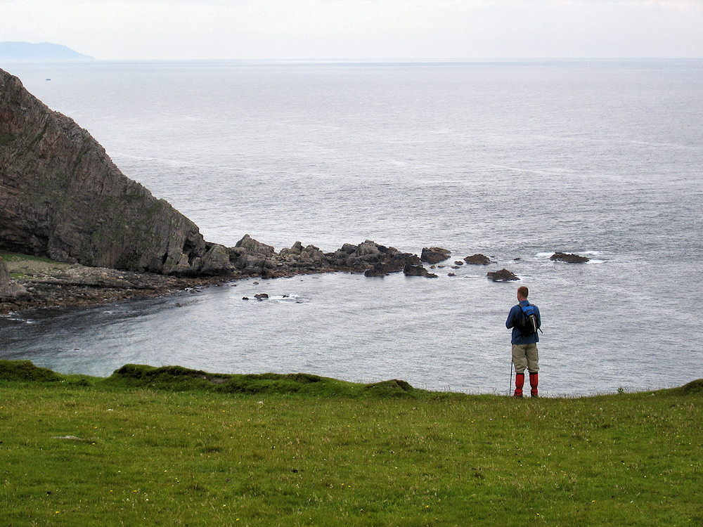 Picture of a man standing on the top of cliffs looking out to sea